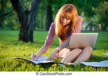 Woman sits on the grass with laptop