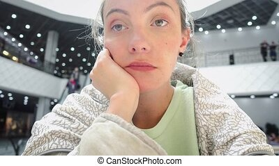 Woman sitting after purchase and feeling tired or bored -...