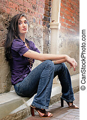 woman sitting against a brick wall