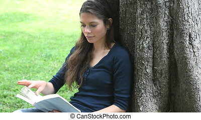 Woman sitting against a tree while