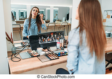 Woman sitting against mirror in beauty studio