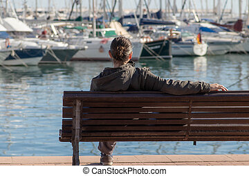 woman sitting alone looking at the sea