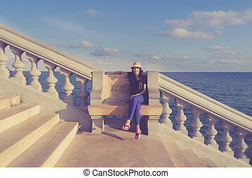 Woman sitting alone on a bench on the promenade of Sitges, Spain
