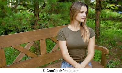 Woman sitting alone on a bench. The attractive girl sits on a wooden bench among greens. Female sitting on a bench in a picturesque place.