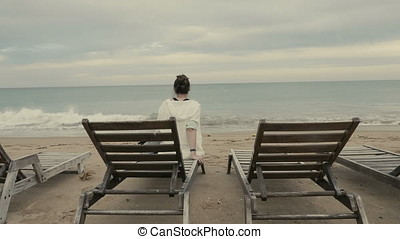 Woman sitting alone on sunbed and looking at the sea at the dusk