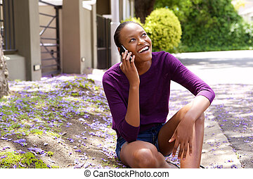 Woman sitting along a street and talking on cell phone