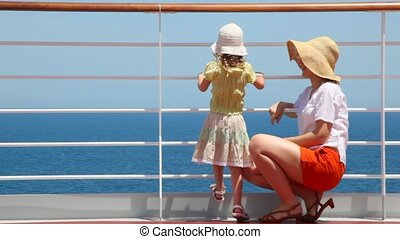 woman sitting and girl standing at railing on deck