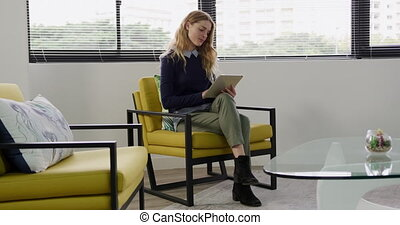 Woman sitting and looking at touch pad