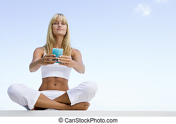 Woman sitting and meditating outdoors while holding a candle