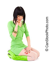 woman sitting and phoned in a short dress