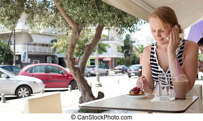 Woman sitting at a cafeteria talking on a mobile - Woman...