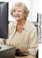 Woman sitting at a computer terminal typing (high key)