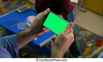 Woman sitting at a desk in class room while a man is watching a smart phone with green screen