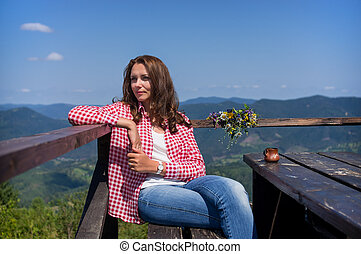 Woman sitting at a table in the mountains