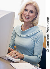 Woman sitting at computer typing (high key)
