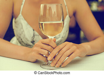 Woman sitting at table with white glass of wine.