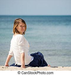 Beautiful blonde woman sitting at the beach