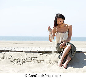 Woman sitting at the beach with sand in hand