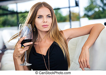Woman sitting at the restaurant with glass of red wine