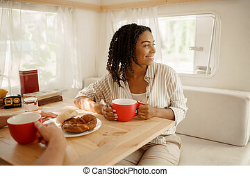Woman sitting at the rv table, camping in trailer