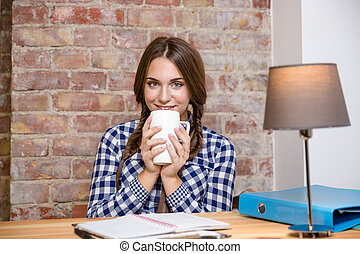 Woman sitting at the table and drinking tea