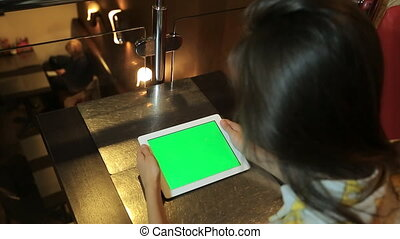 woman sitting at the table and holding tablet filled green. chroma key keying