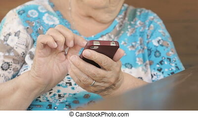 Woman sitting at the table holds a cell phone