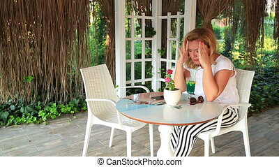 Woman sitting at the table in summer cafe witn a phone and waiting to somebody
