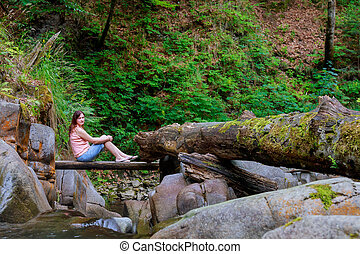 Woman sitting at the wood bridge