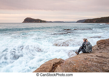 Woman sitting by the ocean letting waves lap at her feet