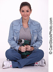 Woman sitting cross-legged and holding an electric screwdriver