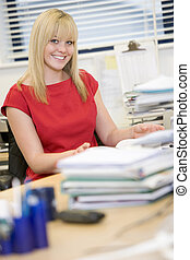 Woman sitting happily at her desk