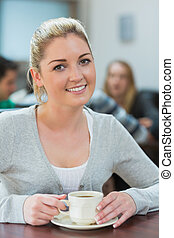 Woman sitting holding a cup of coffee in college cafe