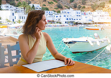 woman sitting in a cafe at a table on beach