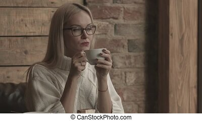 Woman sitting in a cafe. Looking away drinking coffee