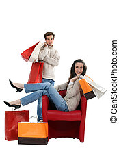 Woman sitting in a chair and surrounded by shopping bags