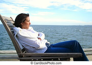Woman sitting in a chair by the waterfont