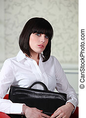 Woman sitting in a chair with a briefcase