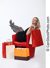 Woman sitting in a chair with shopping bags