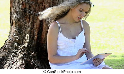 Woman sitting in a park using an eb