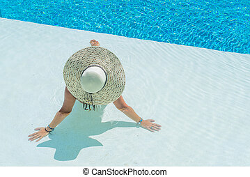 Woman sitting in a swimming pool in a sunhat