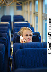 Woman sitting in a train talking on her mobile