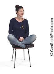 woman sitting in a vintage chair with the lotus pose