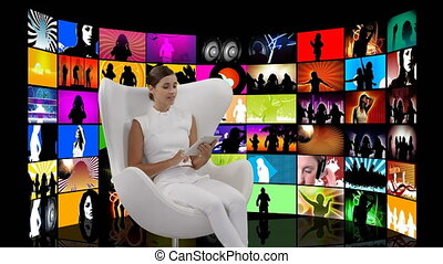 Woman sitting in a white chair and videos on screens