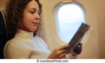Woman sitting in armchair of airplane and reading magazine -...