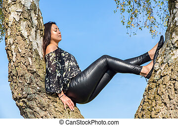Woman sitting in birch tree with sky