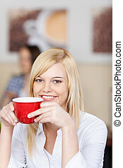 woman sitting in cafe and holding coffee cup
