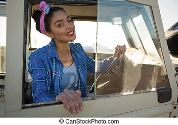 Woman sitting in car at countrysid