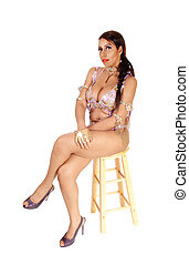 Woman sitting in carnival outfit in full length on chair