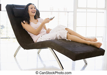 Woman sitting in chair using remote control smiling